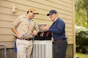 two-professionals-looking-over-air-conditioner