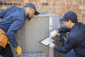 two-technicians-working-on-ac-outdoor-unit