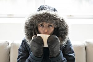 woman-inside-with-parka-on-drinking-from-mug
